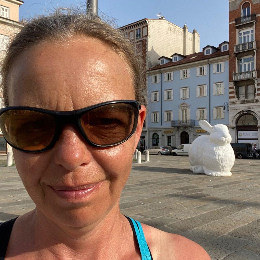 Frau mit Sonnenbrille und Hase im Hintergrund