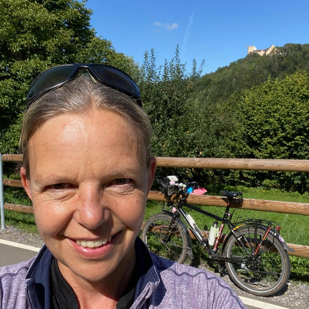 Frau mit Fahrrad und Weitenburg im Hintergrund
