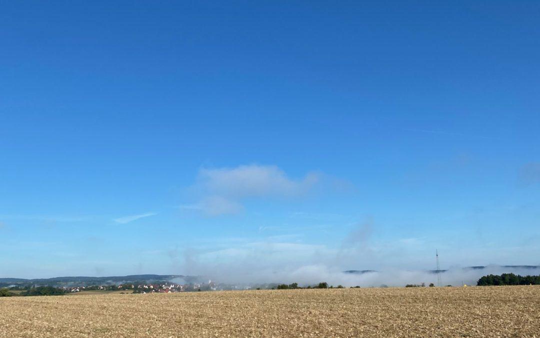 Blauer Himmel mit Feld und Nebel
